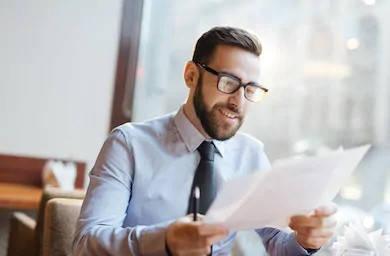 hombre leyendo papeles de certificado